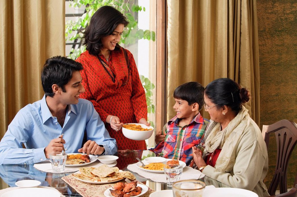 woman serves dinner to her family : Stock Photo