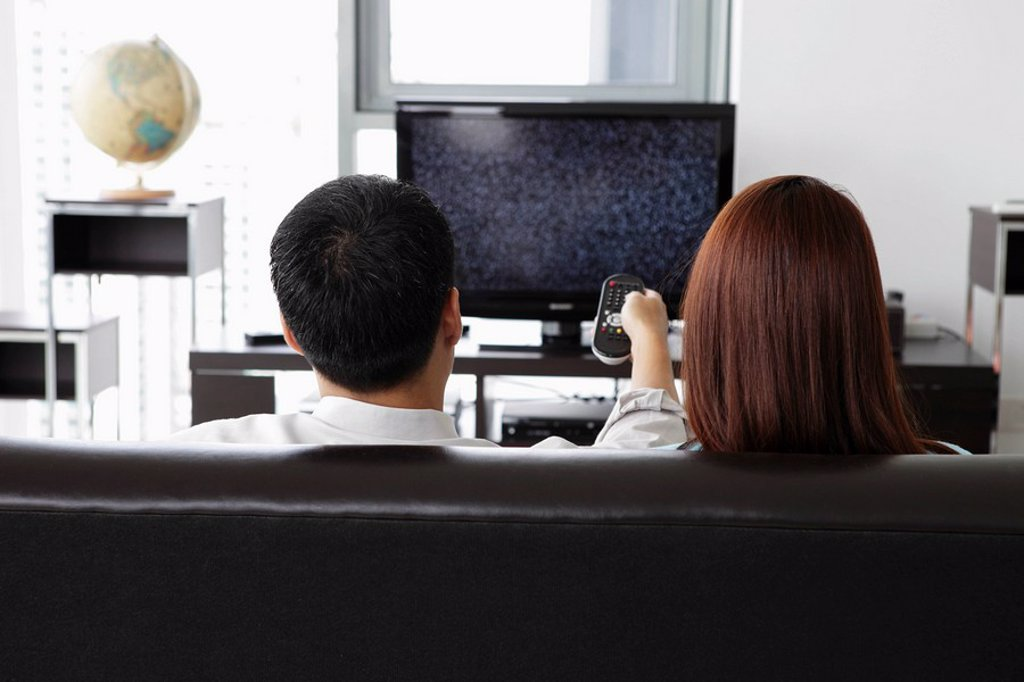 Back view of young couple watching TV at home : Stock Photo