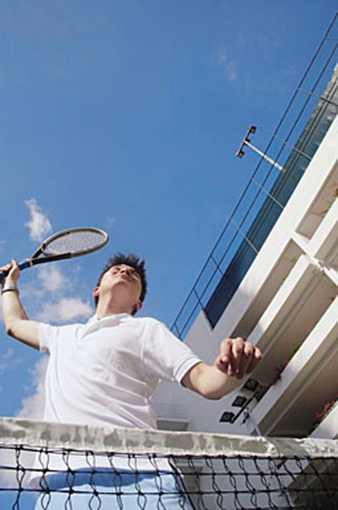Man playing tennis, low angle view : Stock Photo