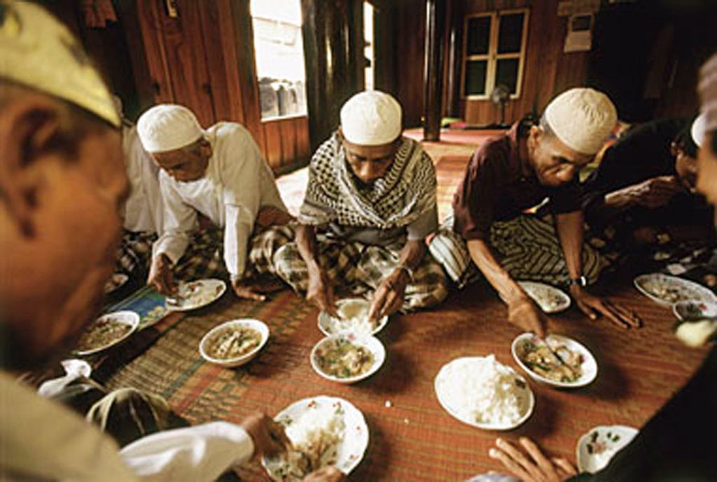 Stock Photo: 4065-16452 Cambodia, Phnom Penh, Muslims celebrating the return of pilgrims with a meal of rice and curry.