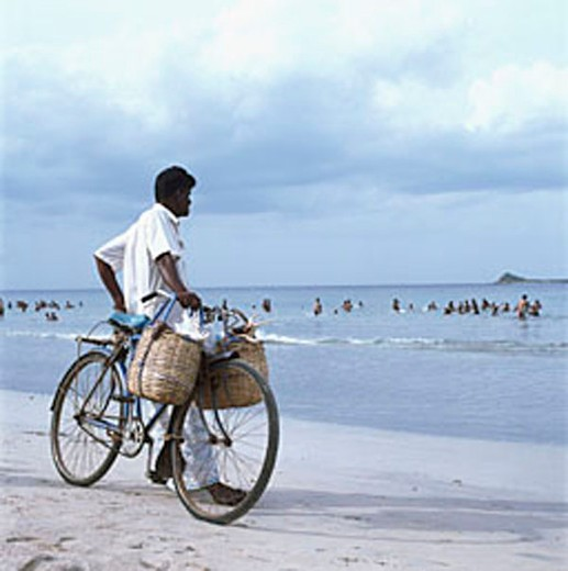 Stock Photo: 4065-16498 Sri Lanka, Trincomalee, local man selling sea shells, with bicycle, o beach