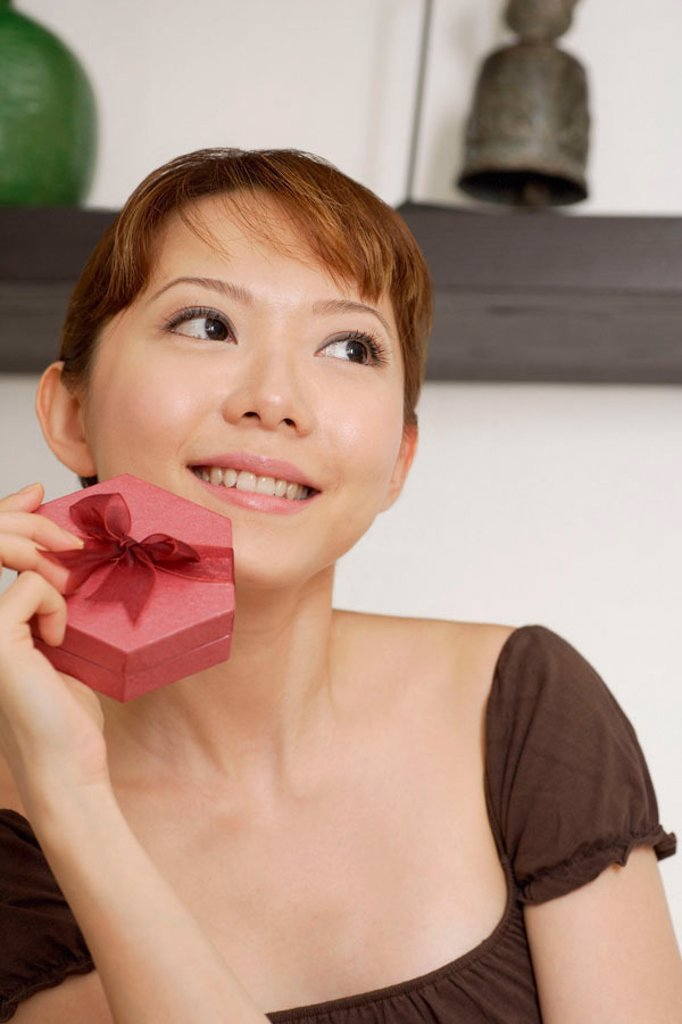 Woman holding gift box, looking away : Stock Photo