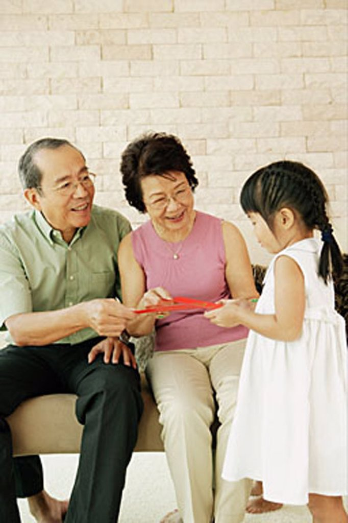 Grandparents giving granddaughter red packets : Stock Photo