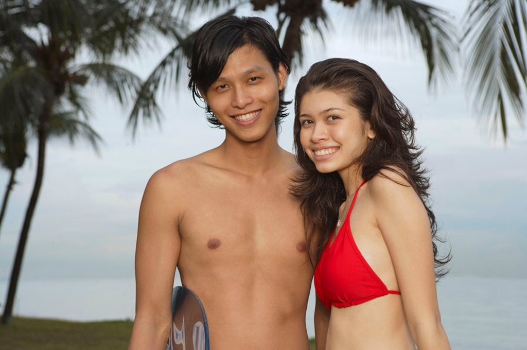 Stock Photo: 4065-16697 Couple on beach, looking at camera, portrait