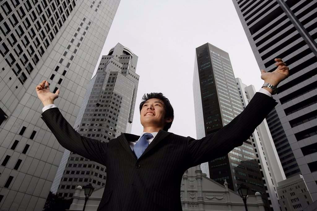 Businessman raising arms in air : Stock Photo