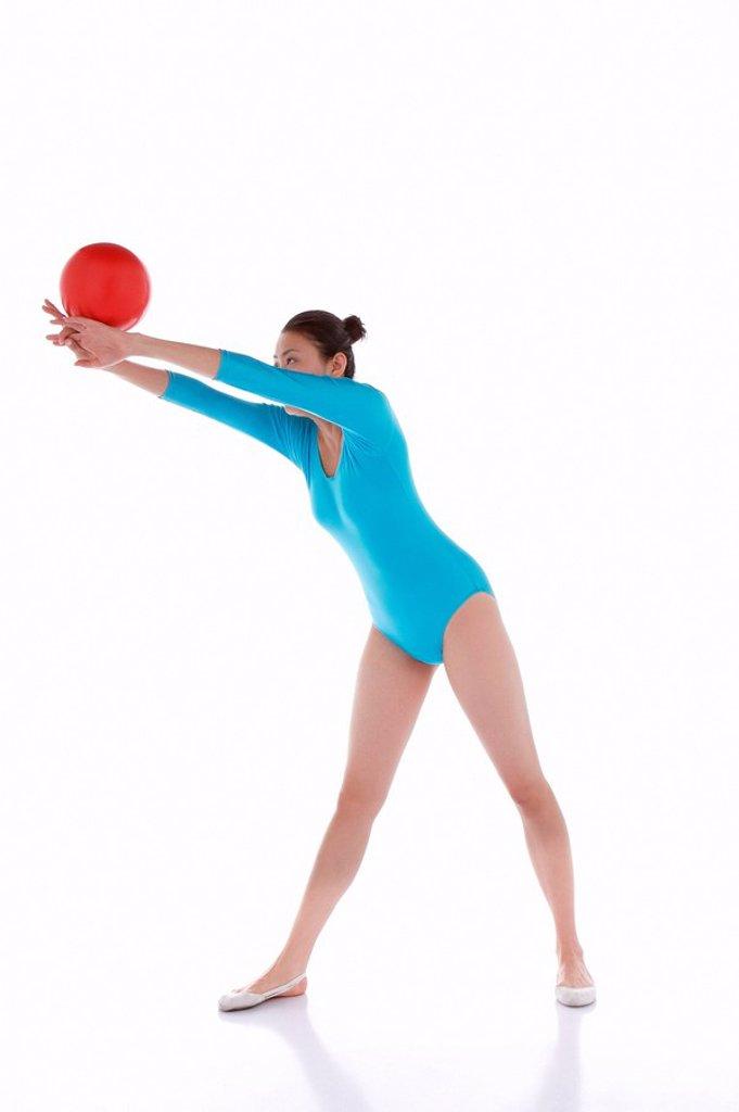 Gymnast performing rhythmic gymnastics with ball : Stock Photo
