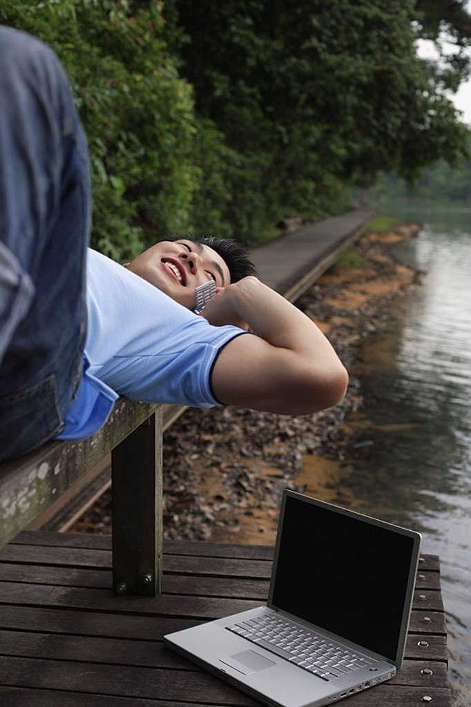 Man using mobile phone, lying on jetty, laptop next to him : Stock Photo