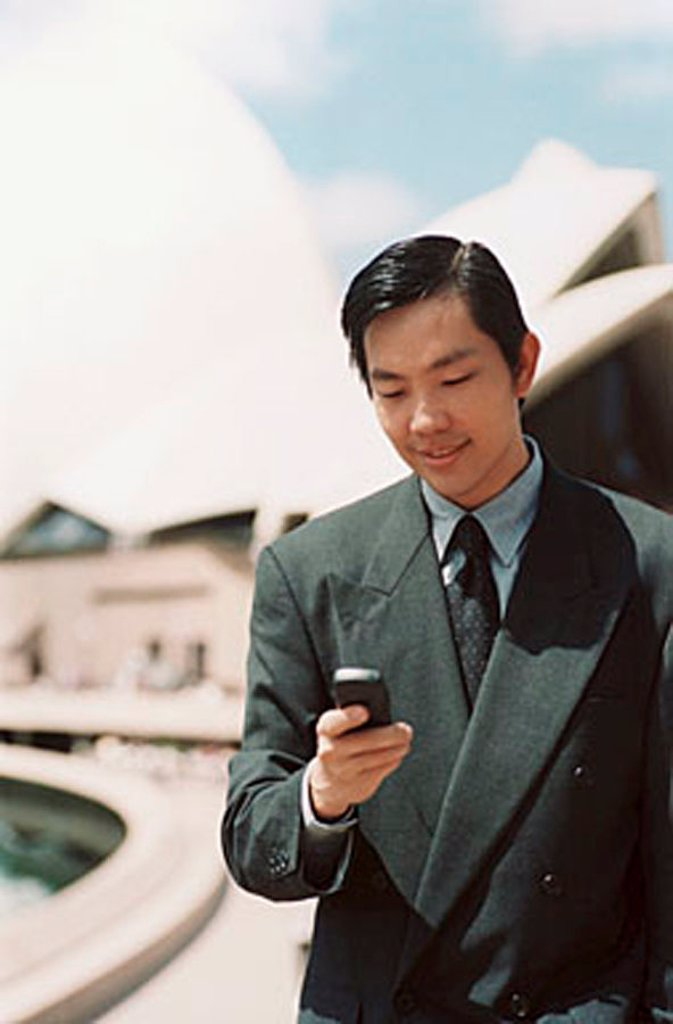 Executive using cellular phone, Sydney Opera House in background : Stock Photo