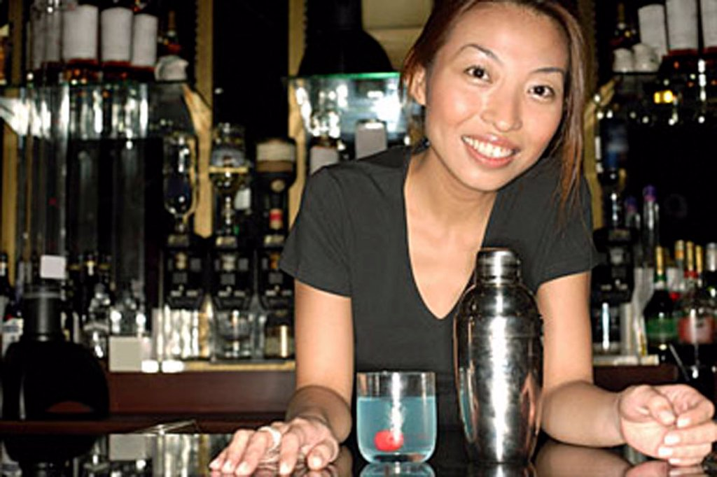 Bartender leaning on counter, looking at camera : Stock Photo