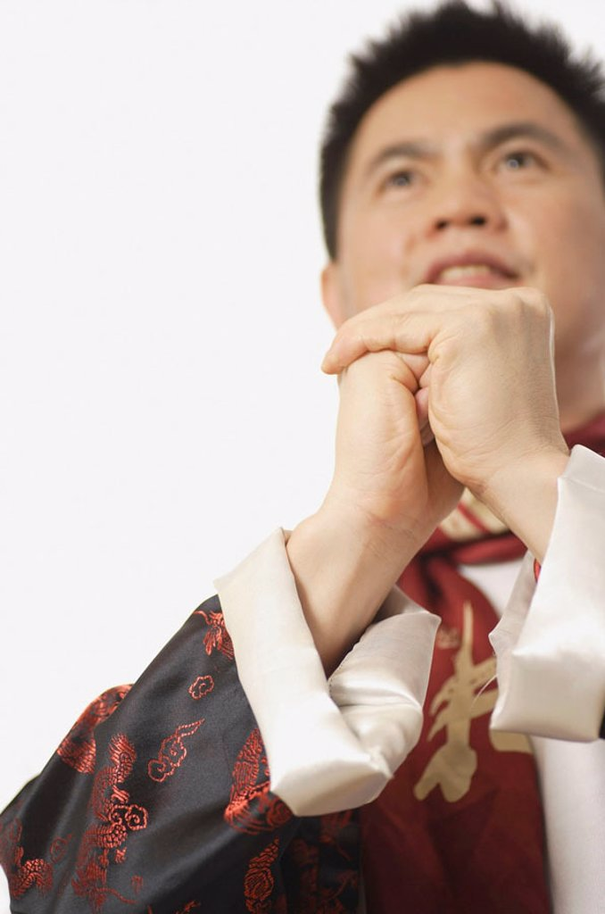 Stock Photo: 4065-1792 Man in Chinese costume, hands clasped