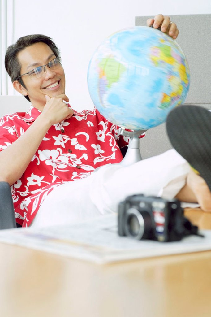 Man in printed shirt sitting in office, feet up on desk, looking at globe : Stock Photo