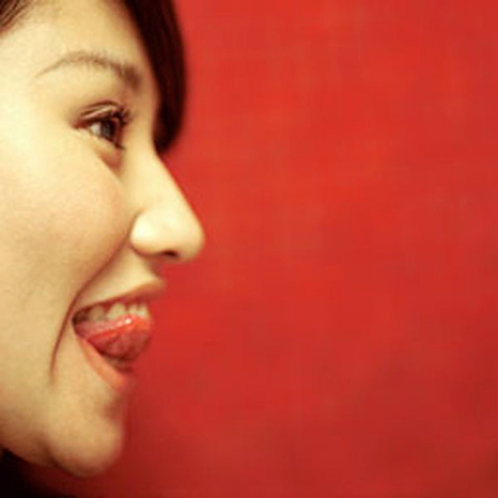 Profile of young woman sticking out tongue, orange/red background. : Stock Photo