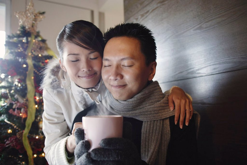 Couple at home, dressed in winter wear, holding mug : Stock Photo