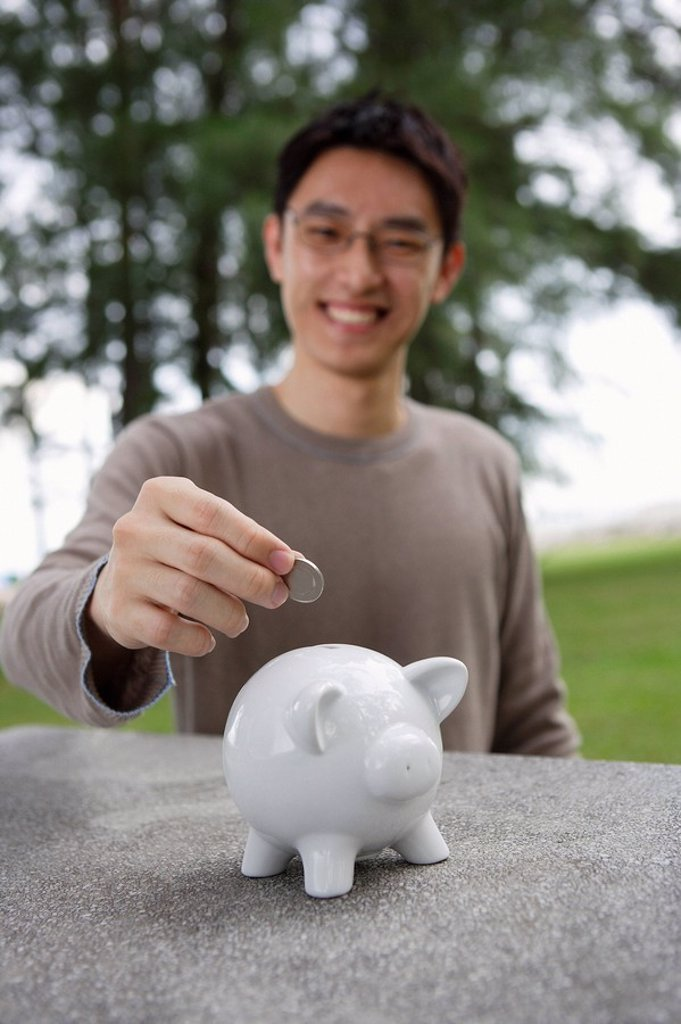 Man putting coin into piggy bank : Stock Photo