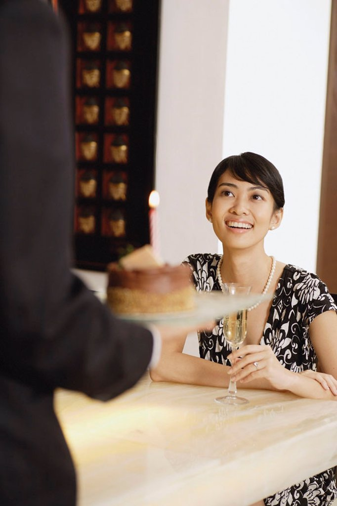 Stock Photo: 4065-18378 Woman sitting at table with Champagne glass, man serving her a cake