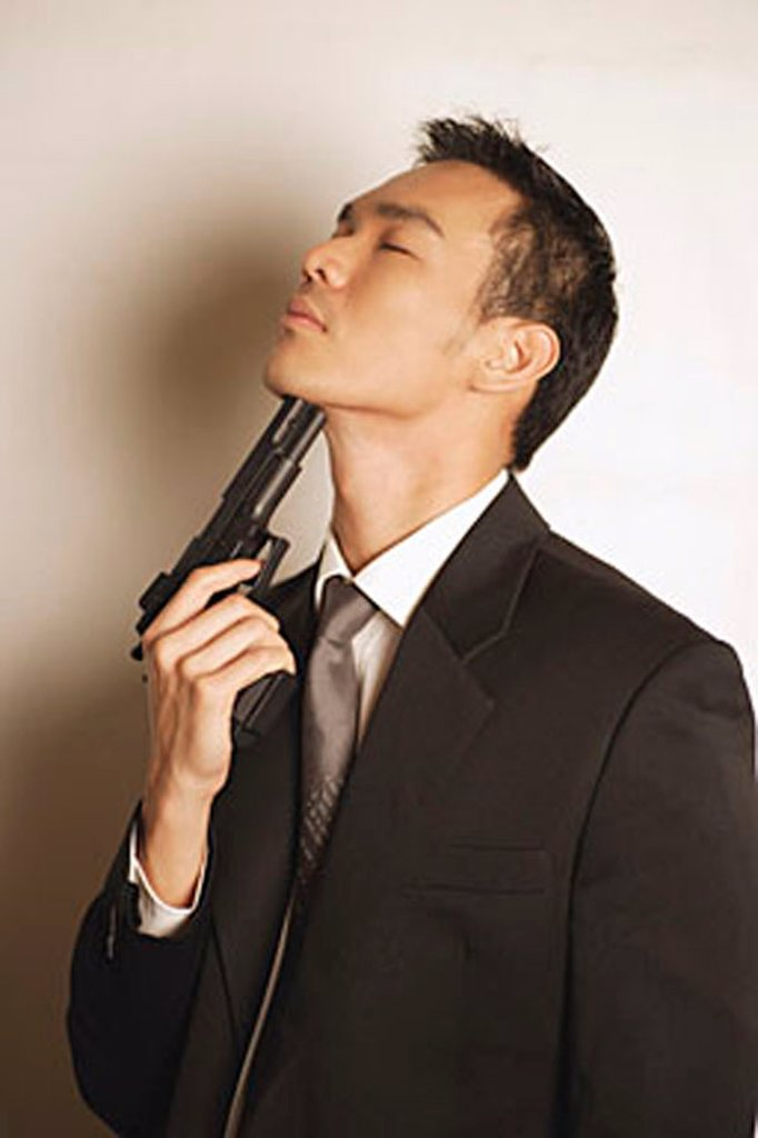Stock Photo: 4065-18481 Man dressed in suit, pointing gun at chin