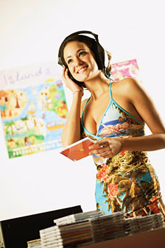 Young woman at home listening to music, hand on head : Stock Photo
