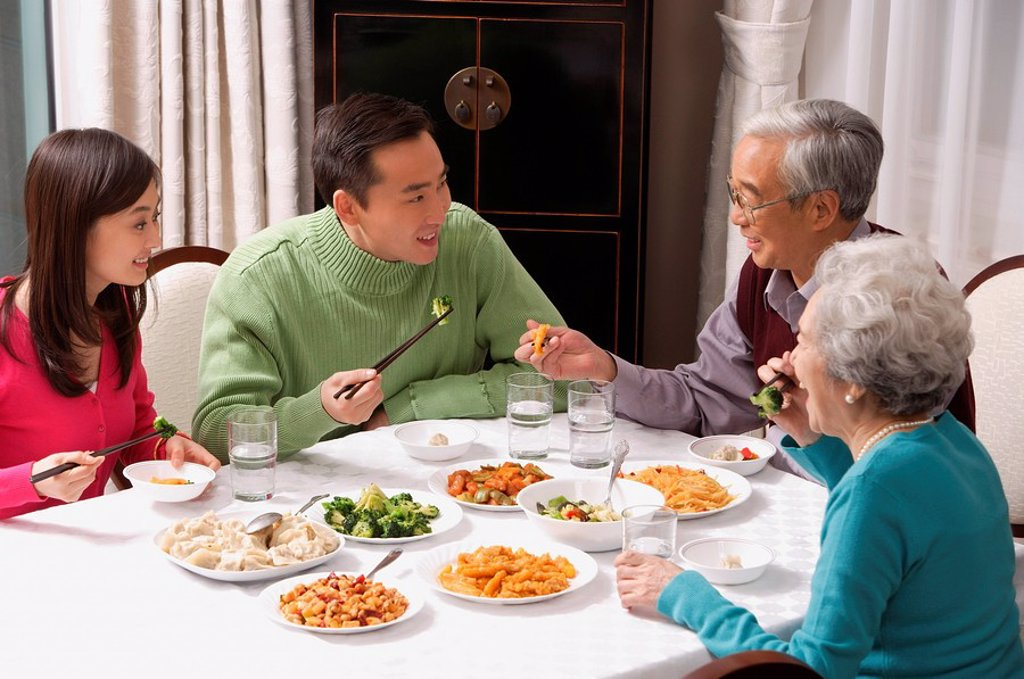 Family at dinner table having traditional food : Stock Photo