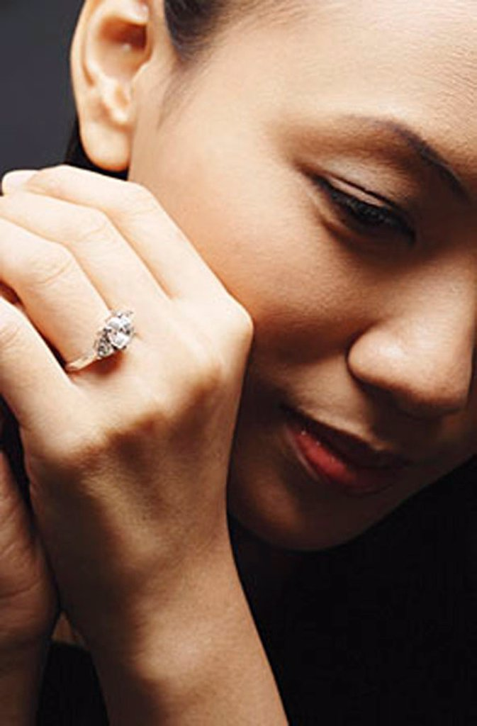 Young woman with ring on finger, head shot : Stock Photo