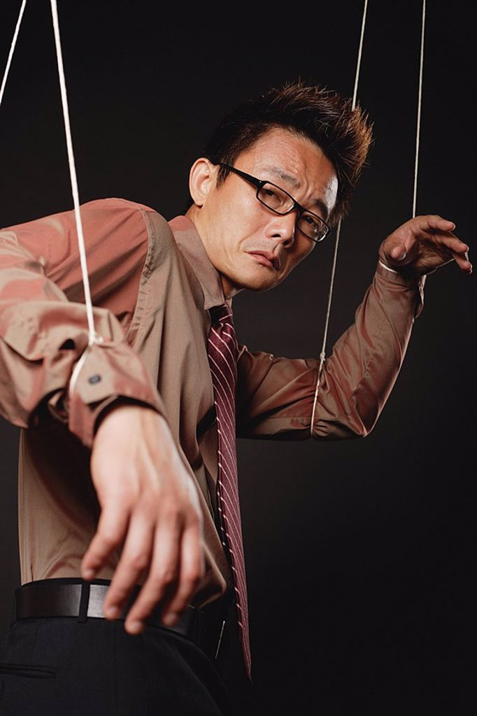 Stock Photo: 4065-19191 Man with marionette strings attached to his hands, looking at camera, frowning