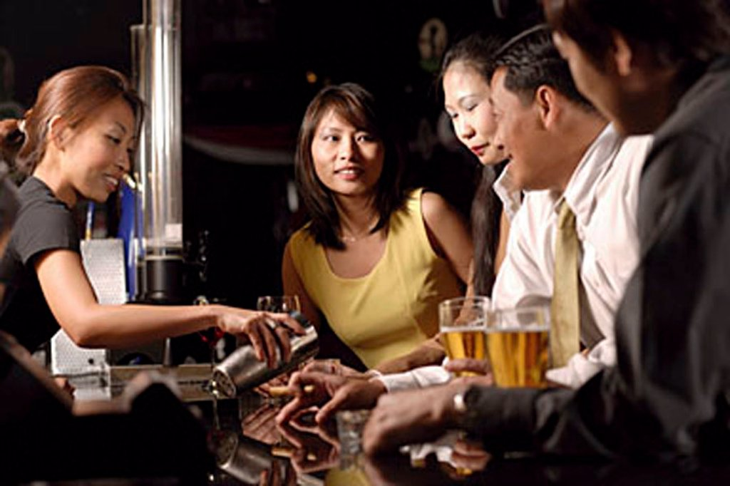 Stock Photo: 4065-19270 Couples at bar counter, bartender pouring drinks
