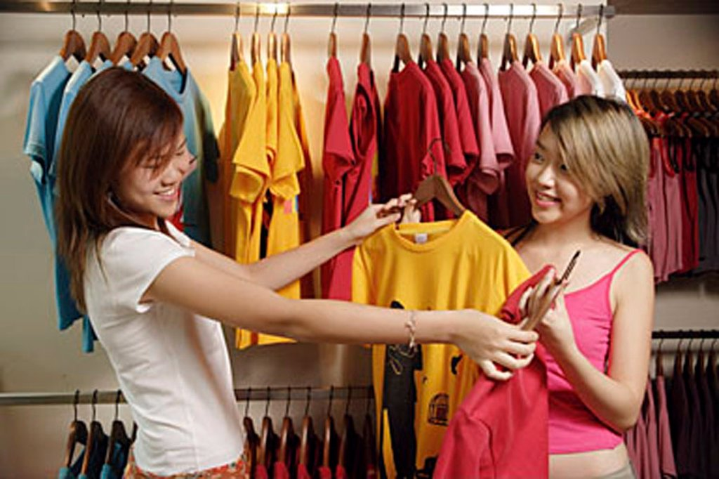 Young women at clothes shop looking at T shirts : Stock Photo