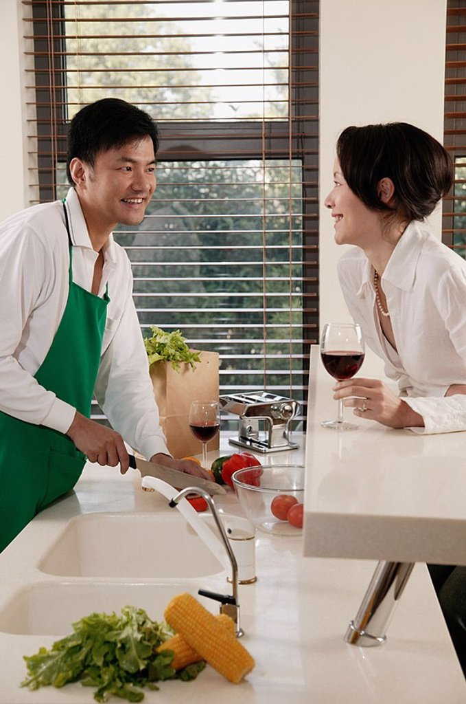 Stock Photo: 4065-19780 Couple in kitchen, man chopping vegetables, woman leaning on counter with wine glass