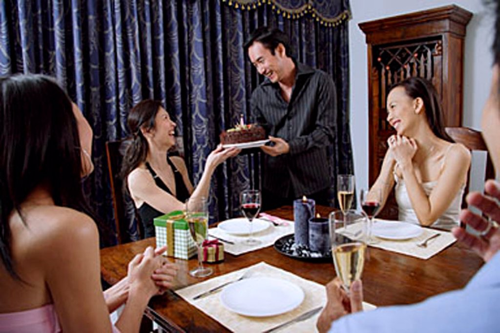 Stock Photo: 4065-19837 Party at home, women accepting birthday cake from man