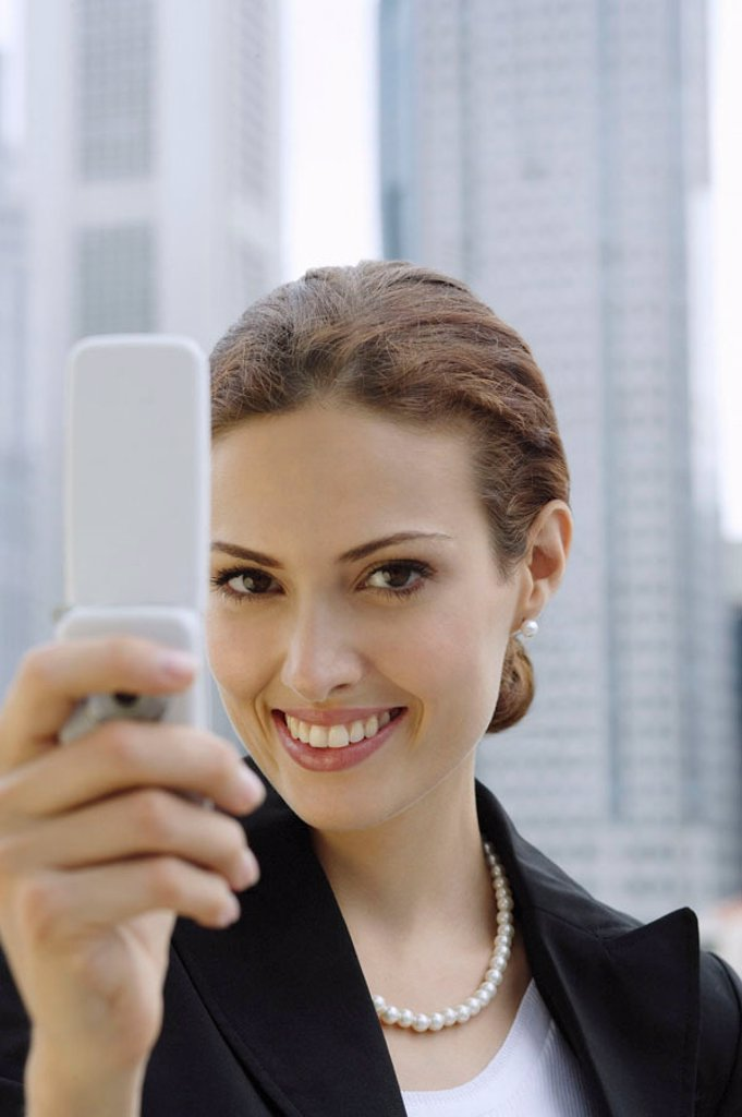 Businesswoman using mobile phone, photo messaging, looking at camera : Stock Photo
