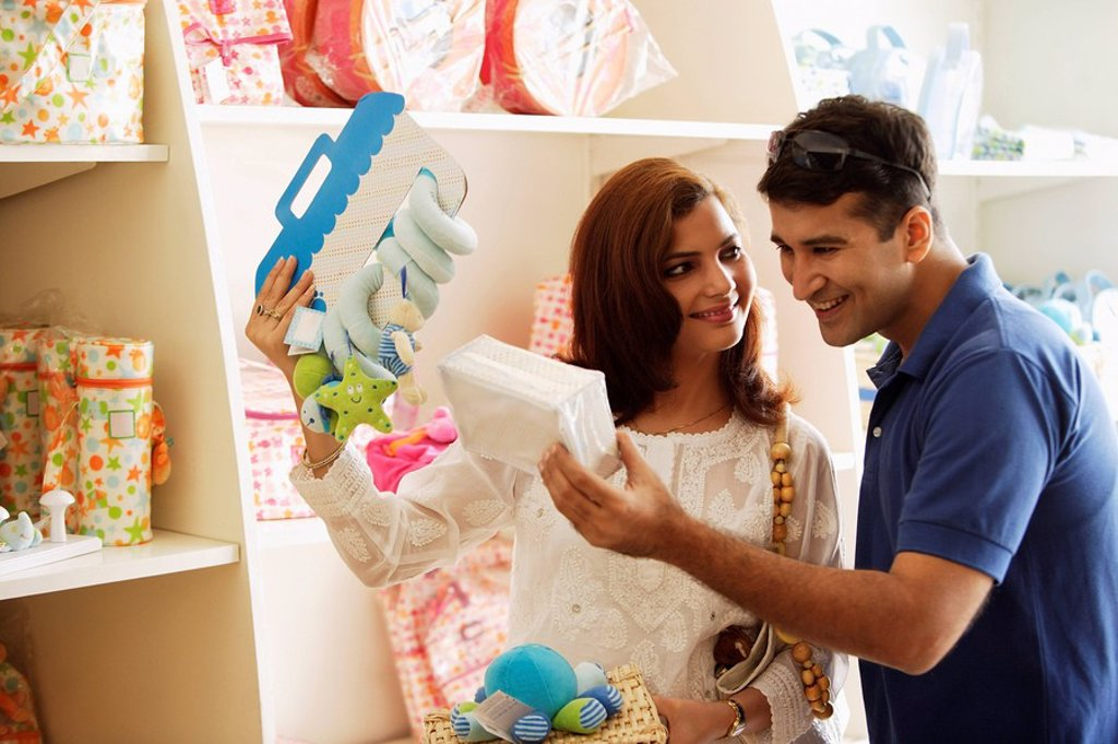 couple looking at baby items : Stock Photo