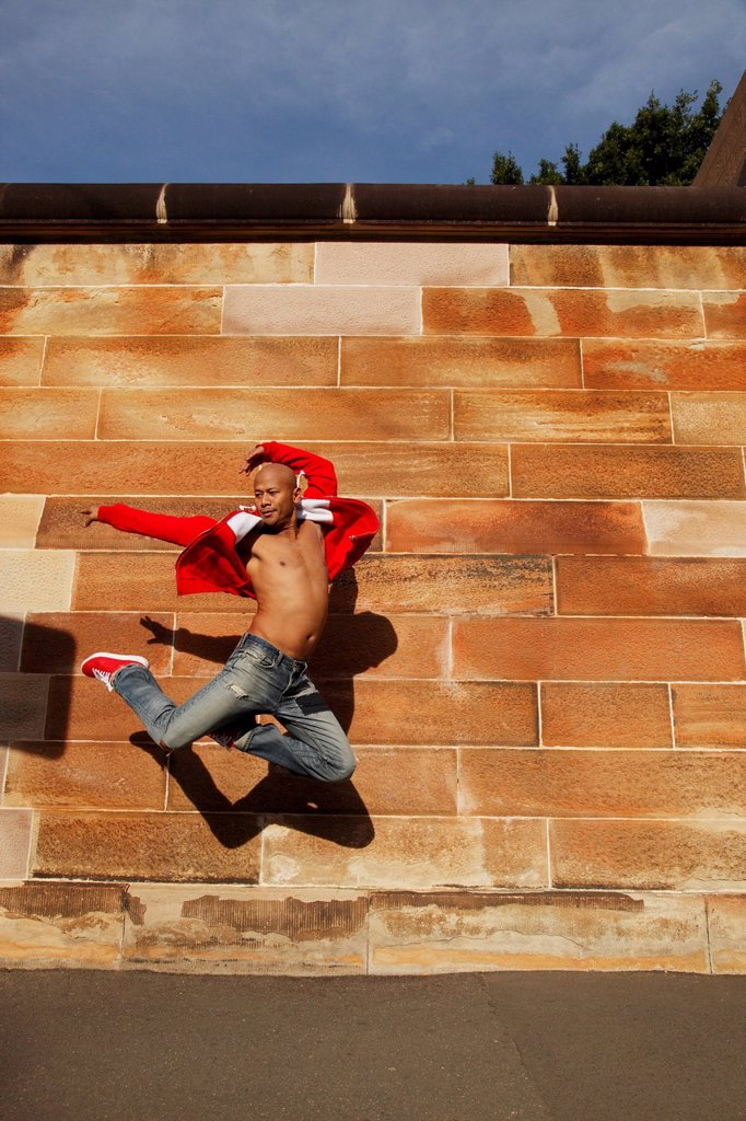 Asian man jumping in air in front of brick wall : Stock Photo