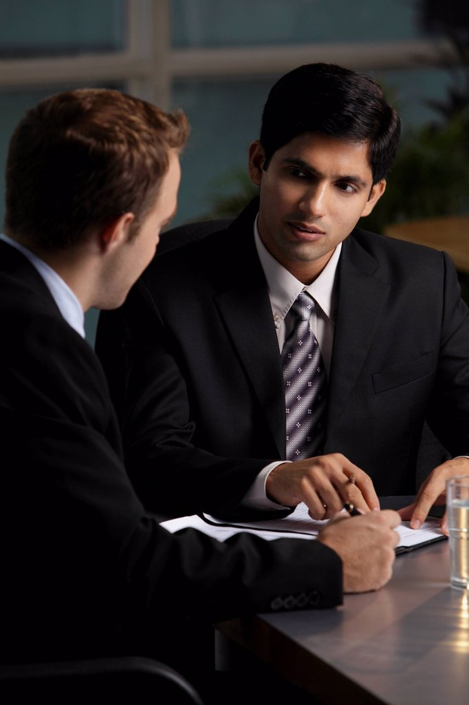 Caucasian man talking to Indian man about a document : Stock Photo