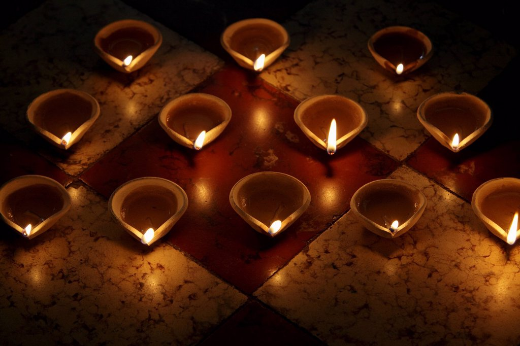 A group of lit clay oil lamps on floor : Stock Photo