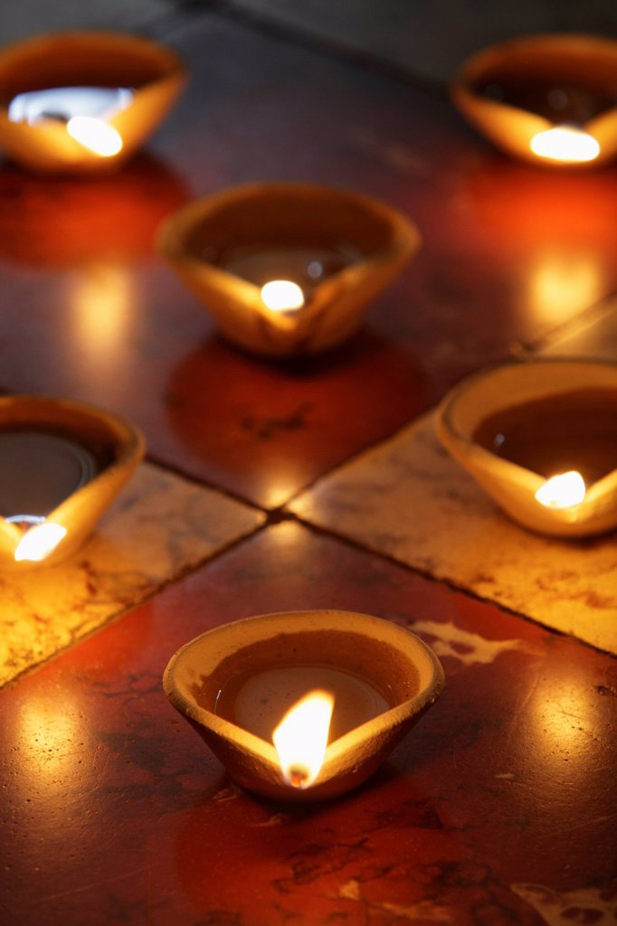 Lit clay oil lamps on floor : Stock Photo
