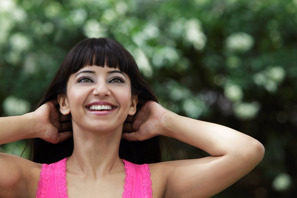 Stock Photo: 4065-20483 Head shot of smiling woman with hands in her hair