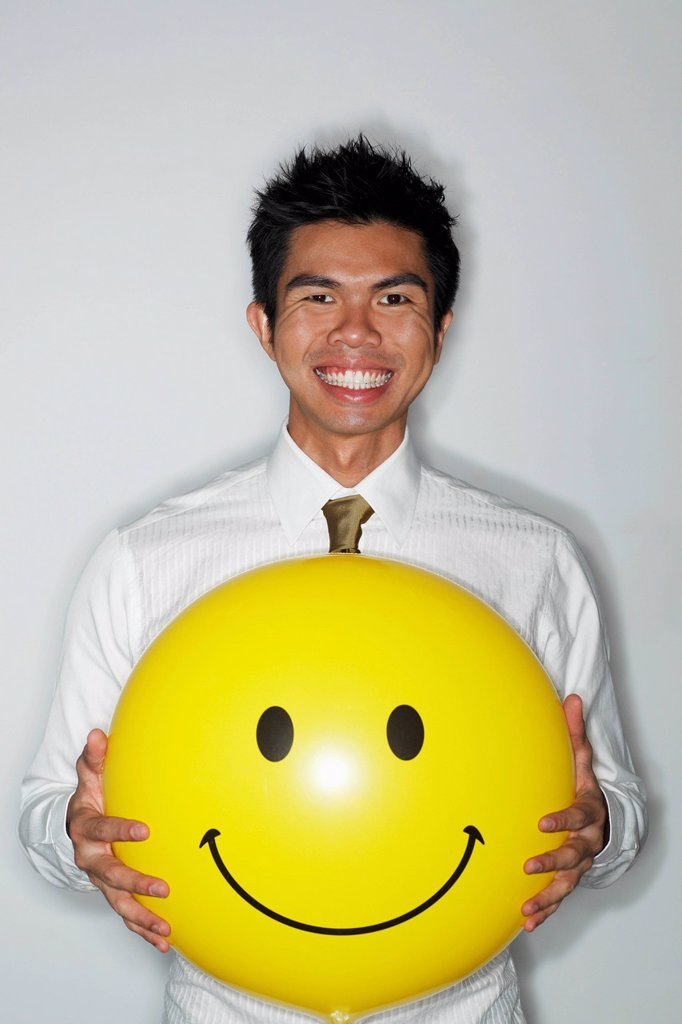 Stock Photo: 4065-20514 young man holding a big smiley face balloon and smiling