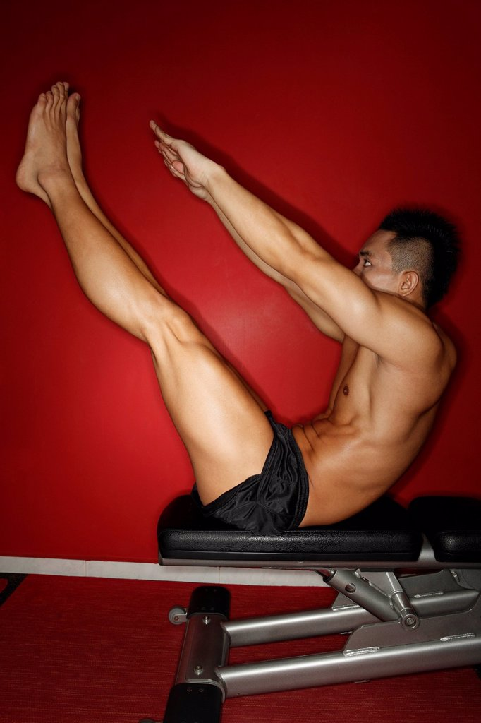 Chinese man stretching in gym : Stock Photo