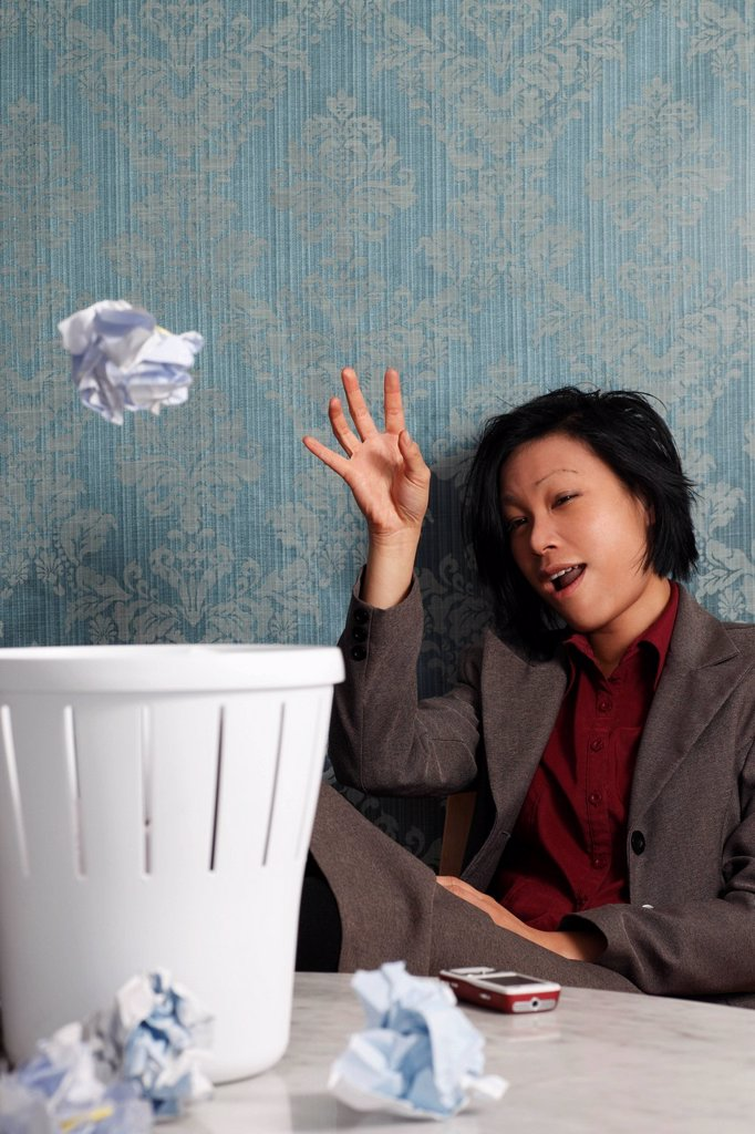 Stock Photo: 4065-20571 Chinese woman throwing paper in a waste basket