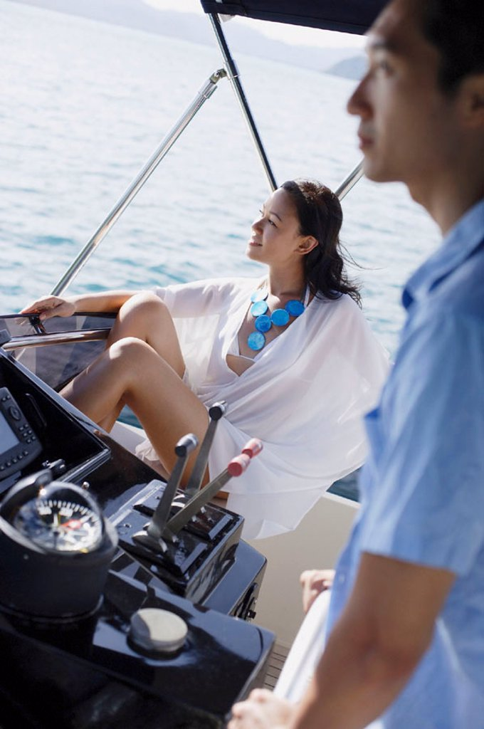 Couple on yacht, man steering, woman sitting and looking away : Stock Photo