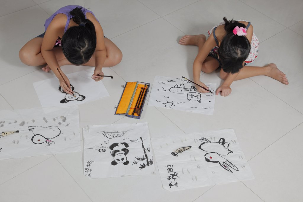 Stock Photo: 4065-20883 Young girls drawing pictures with Chinese brush and ink