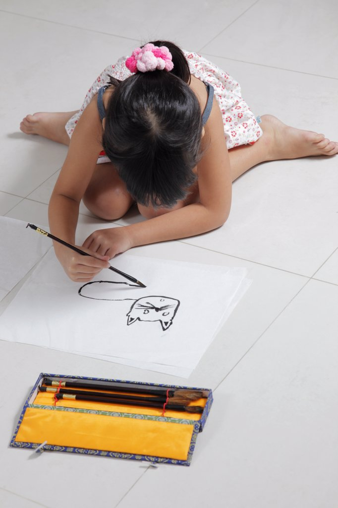 Young girl drawing a cat with Chinese brush and ink : Stock Photo