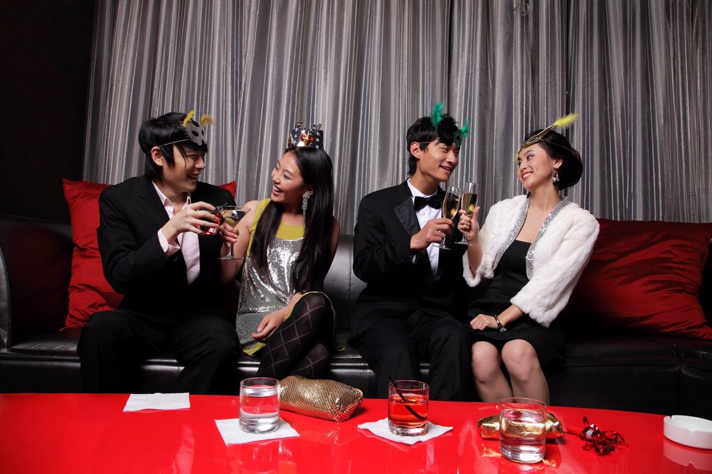 Four people dressed up at a party, toasting each other : Stock Photo