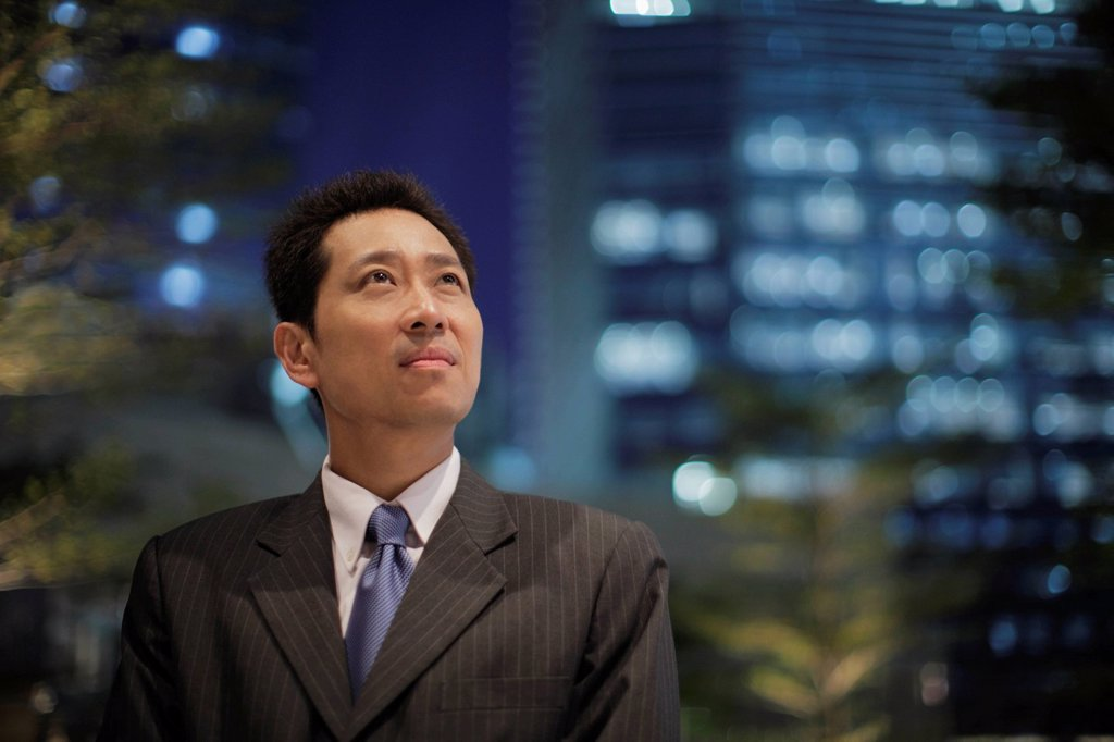 Stock Photo: 4065-22129 mature man wearing a suit in front of lit buildings at night