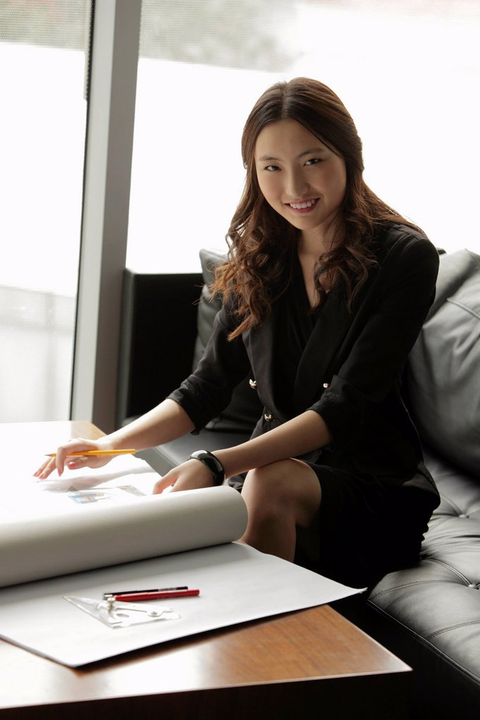 Stock Photo: 4065-22222 Young woman working on plans in an office