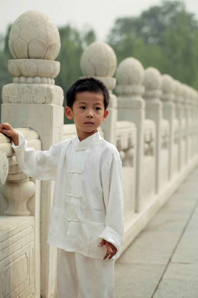 Young boy wearing traditional clothes standing next to stone bridge, : Stock Photo