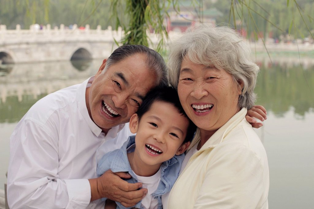 Stock Photo: 4065-22397 Grandma, grandfather and grandson hugging in a park