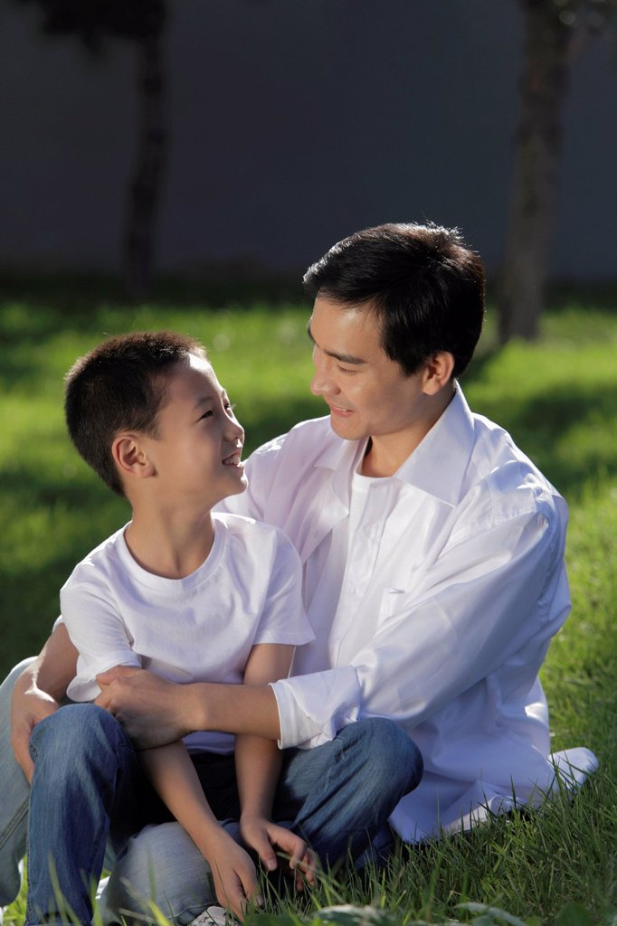 Stock Photo: 4065-22524 Father and son sitting on grass smiling at eachother