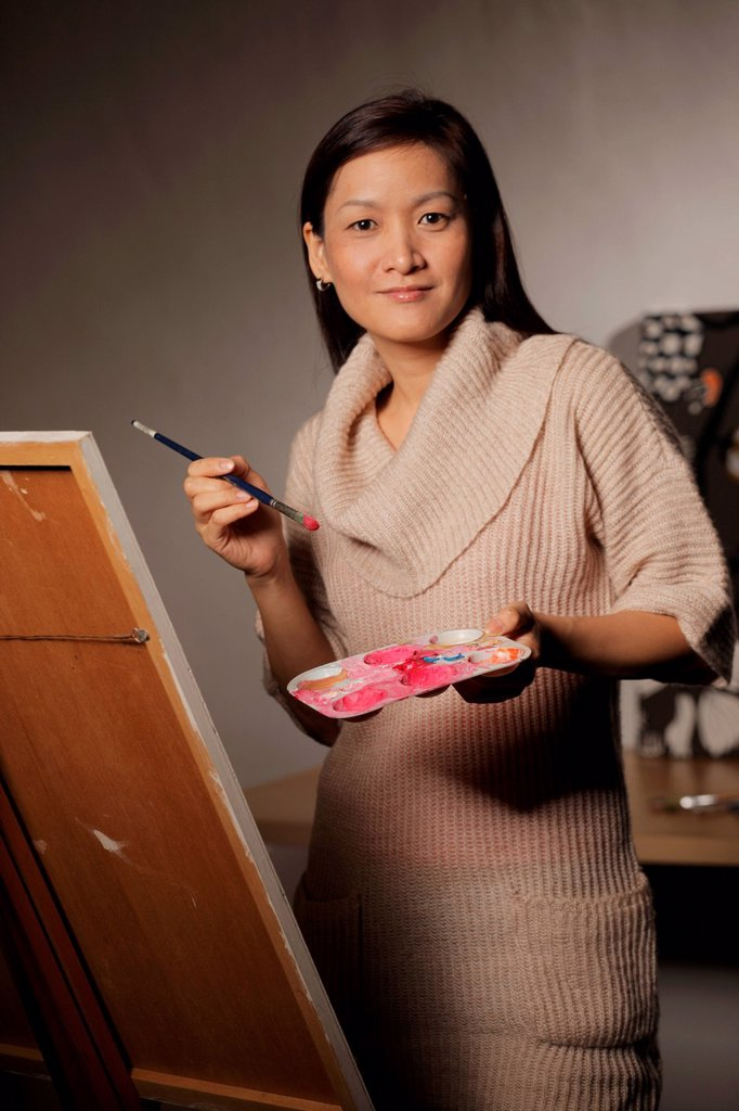 Woman painting on an easel : Stock Photo