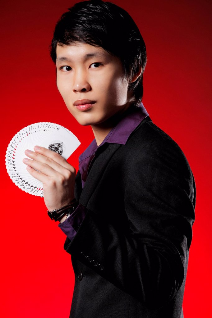 Man wearing a suit holding a deck of cards : Stock Photo