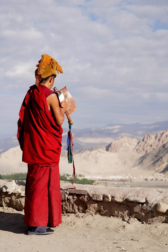 Tibetan monk blowing a horn on the rooftop of the Likir Monastery in Leh, Ladakh, India : Stock Photo